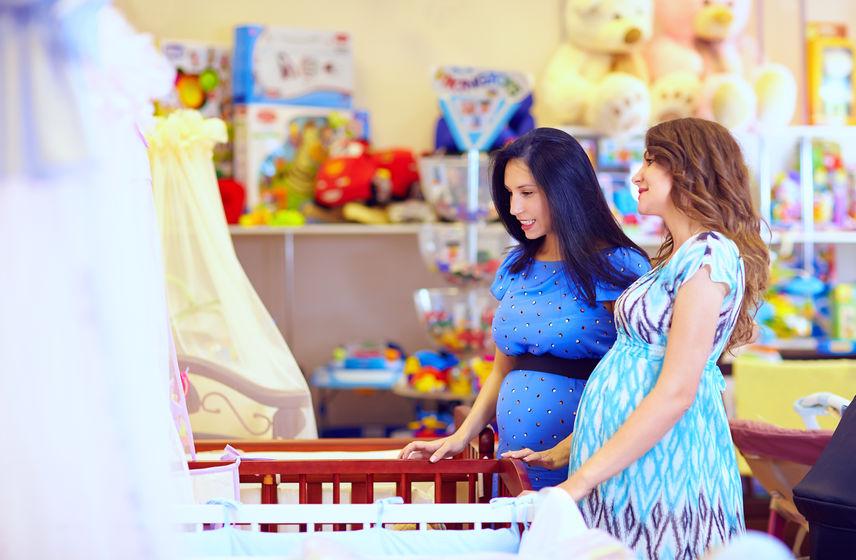 Mulheres grávidas escolhendo o berço em uma loja de enxoval