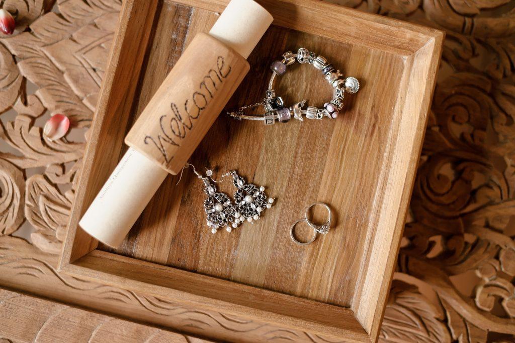 Bandeja de bambu com anéis, brincos e pulseira de berloques apoiados