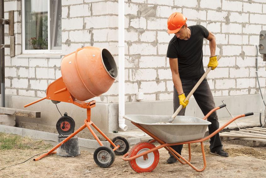 Imagem mostra um homem preenchendo uma betoneira com material para mistura.