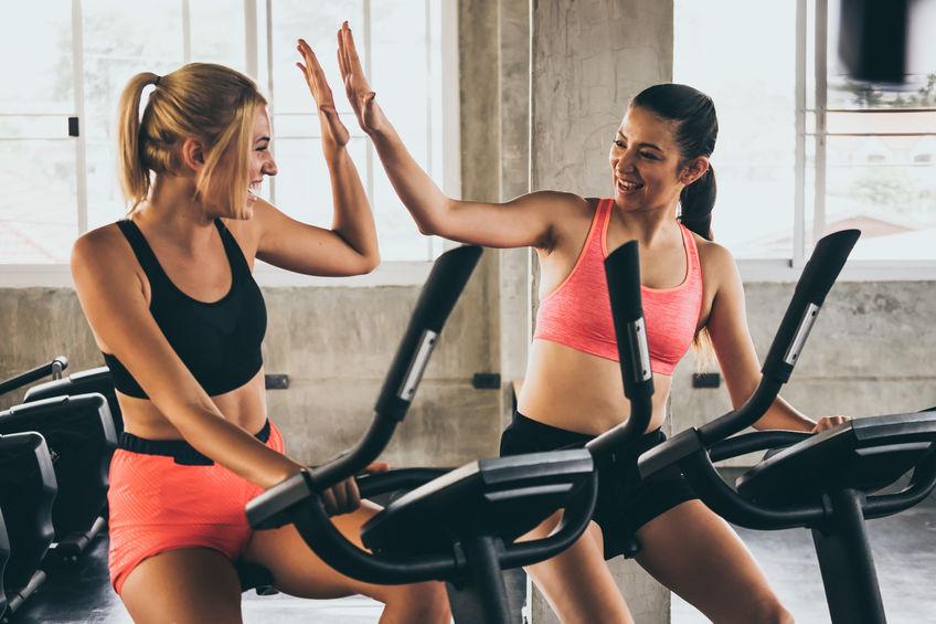 Imagem mostra duas amigas se cumprimentando enquanto sentadas em bicicletas ergométricas horizontais de uma academia.