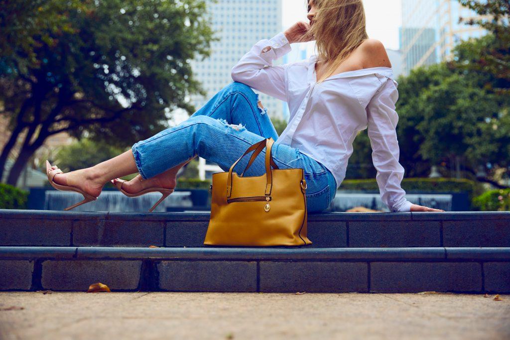 : Imagem de uma mulher sentada, com uma bolsa ao lado.