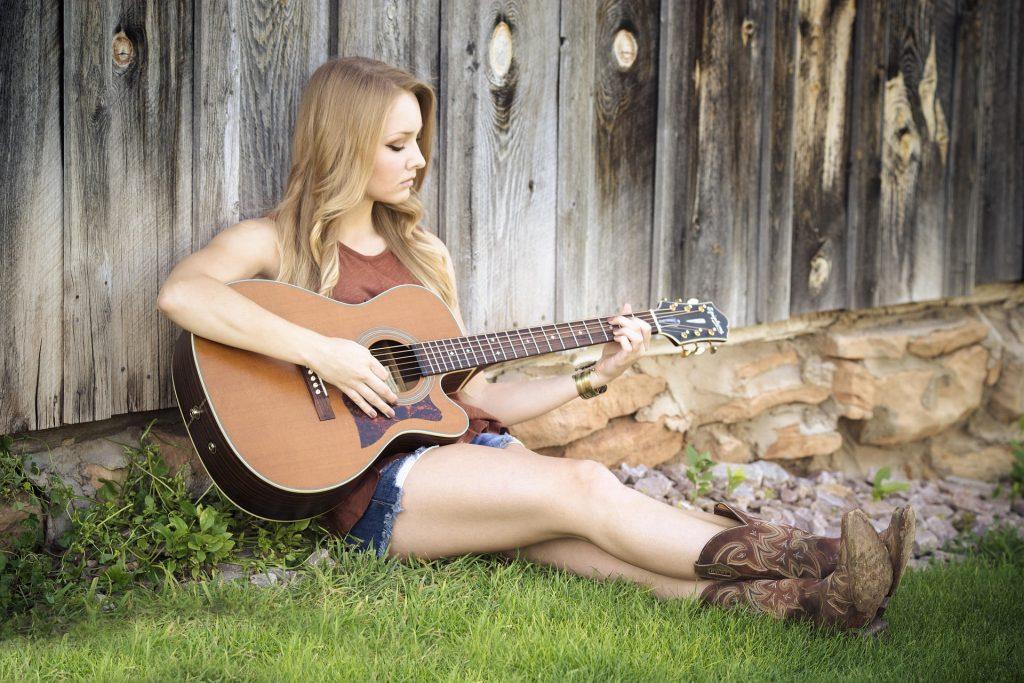 Na foto uma mulher sentada em uma grama com um violão no colo.