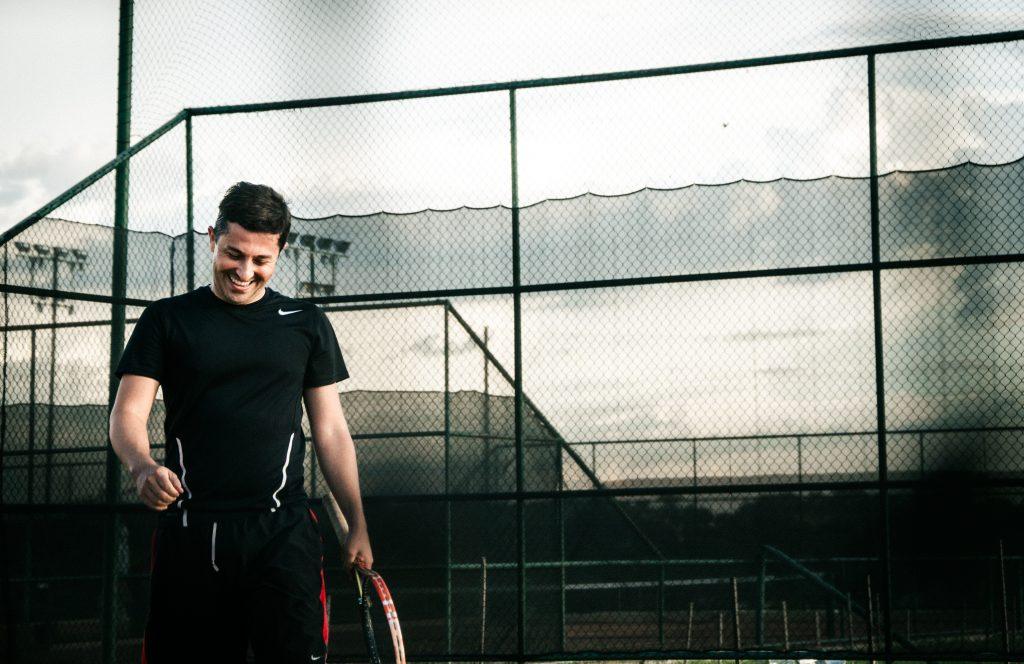 Tenista segurando raquete usando camiseta Nike.