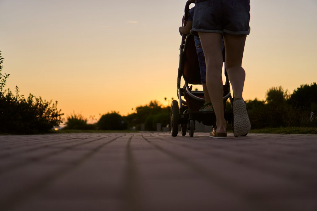 Imagem de costas e com close em pés de mulher andando empurrando um carrinho de bebê.