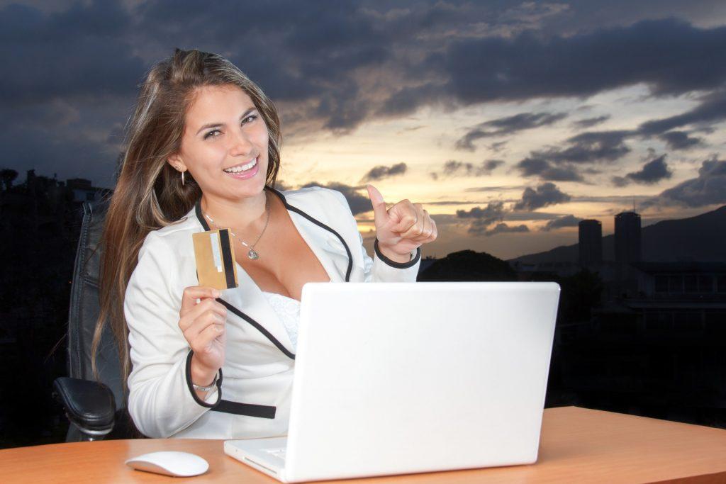 Mulher mostrando o cartão, com notebook à frente.