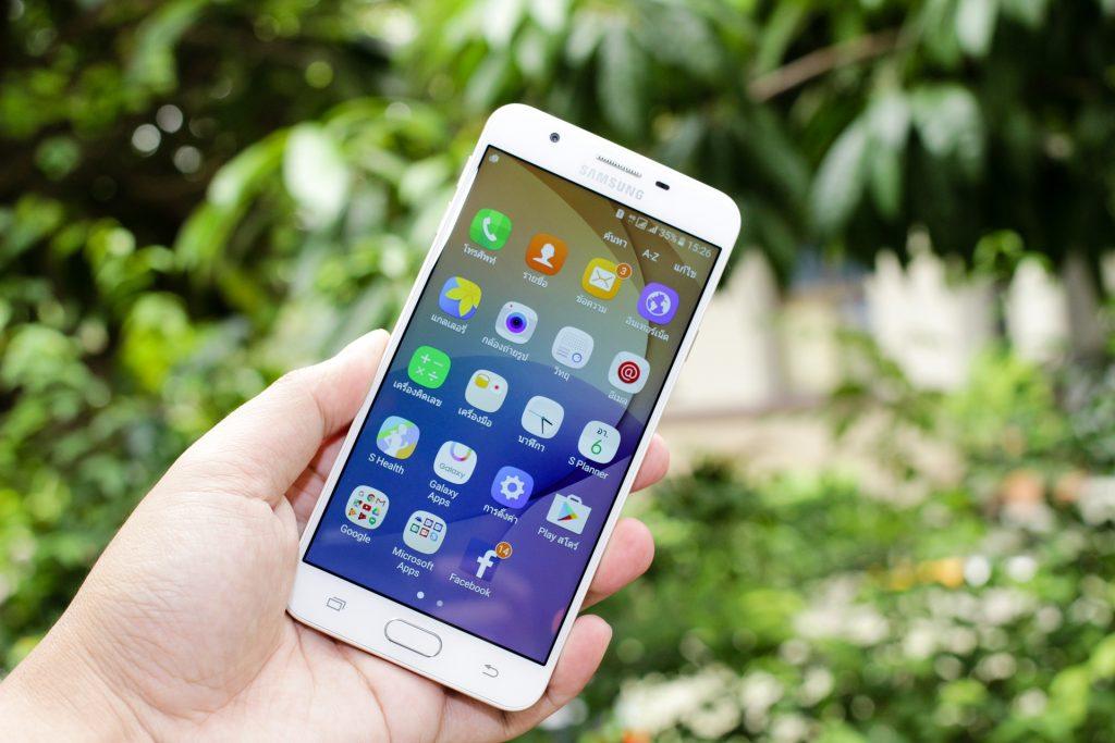 Mão segurando um celular da Samsung.