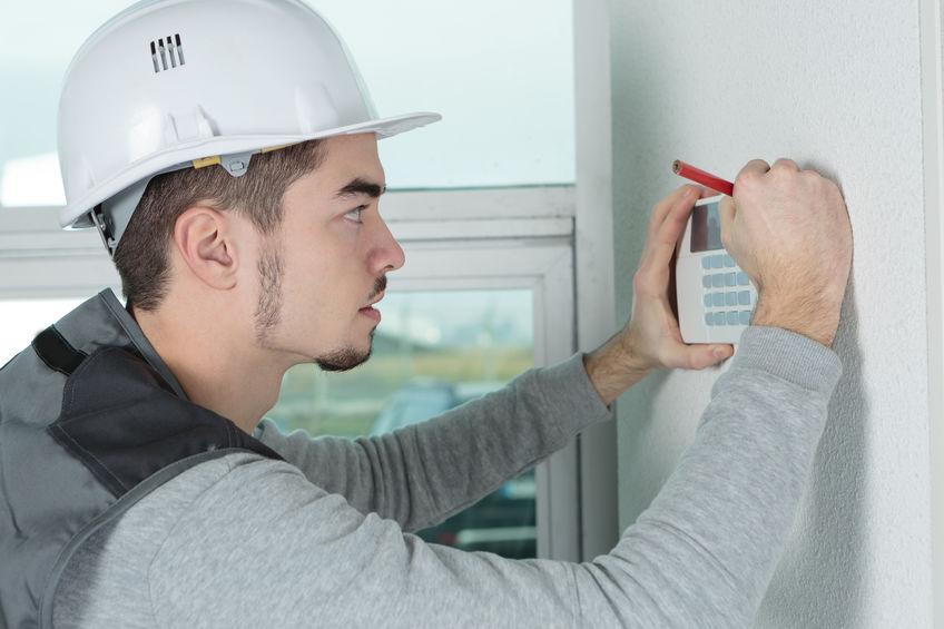 Imagem mostra um homem instalando uma central de alarme.