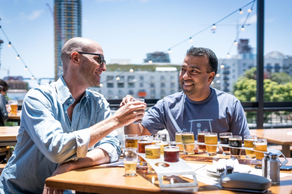 Imagem mostra dois homens sentados à mesa num ambiente externo. A mesa comporta diversos copos de cerveja, de diferentes cores. Os homens brindam com dois desses copos.