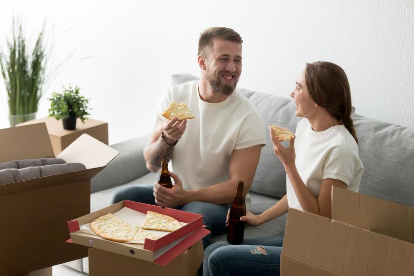 Casal no sofá, comendo pizza e tomando cerveja.