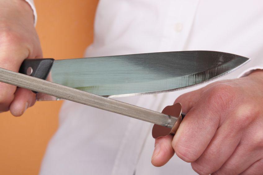 Imagem de pessoa utilizando uma chaira para amolar a faca