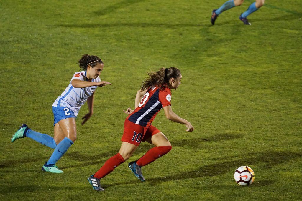 Imagem mostra o momento de um jogo em que uma jogadora, usando a camisa número dois, persegue a sua adversária, com a camisa dez, que corre com a bola.