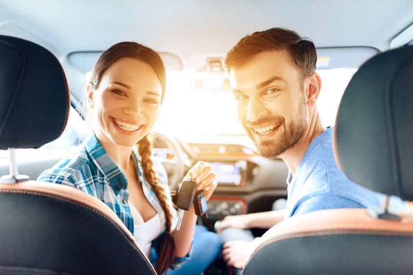 Homem e mulher sentados nos bancos da frente de um carro olhando para trás e sorrindo. A mulher está no volante com as chaves na mão.