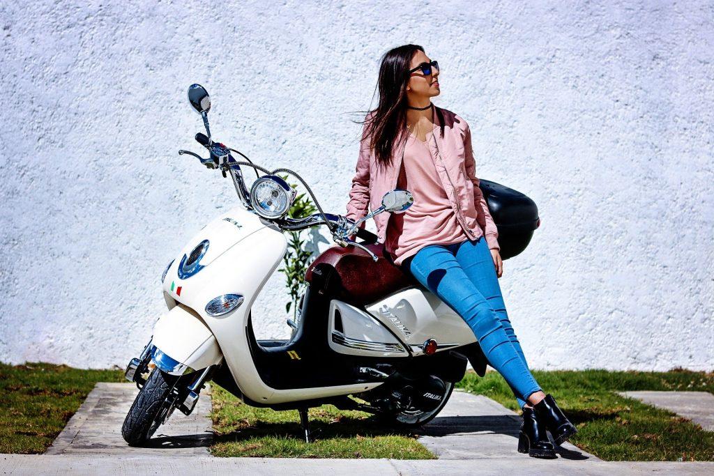 Mulher apoiada em uma motocicleta.