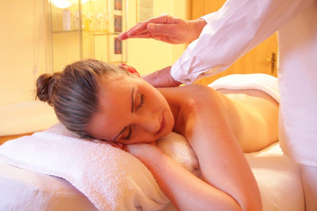 Foto de uma mulher deitada de bruços em uma maca com toalhas, de olhos fechados, recebendo massagem nas costas de um massagista.