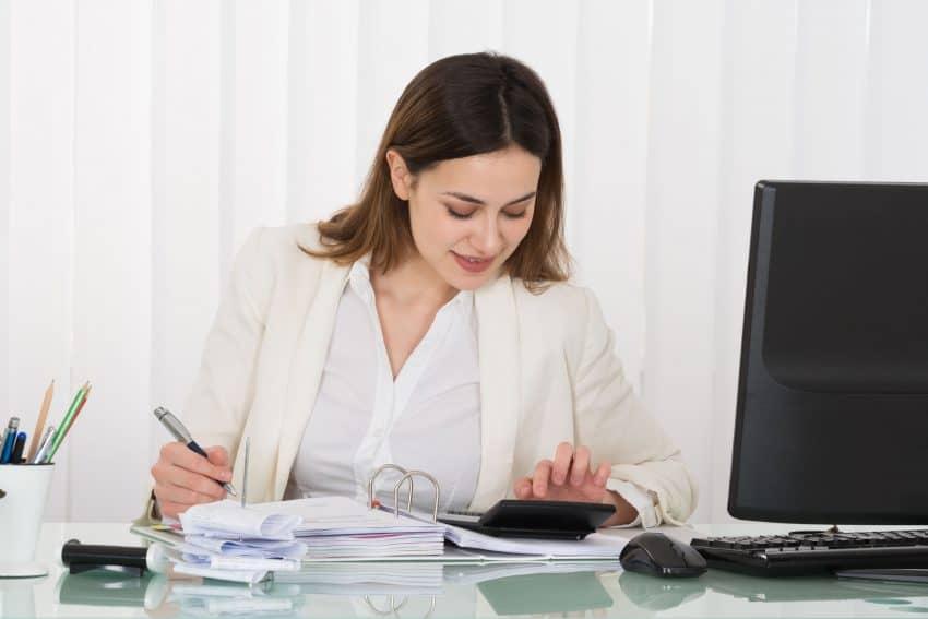 Mulher em escritório, fazendo anotações e usando a calculadora.