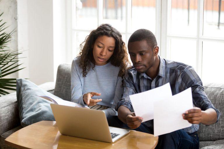 Casal sentado no sofá, de frente para o notebook, segurando folhas de papel.