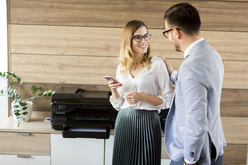 Imagem de duas pessoas conversando ao lado de uma impressora.