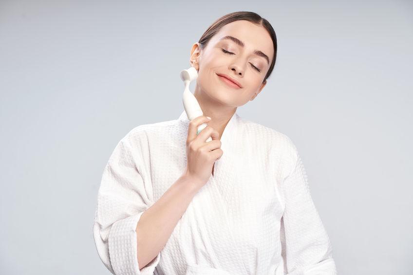 Imagem de uma mulher de roupão segurando uma escova de limpeza facial perto do rosto.