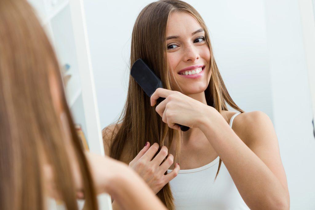 Mulher de cabelos castanhos longos se penteia em frente a um espelho