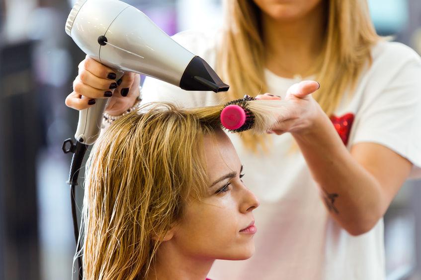 Na foto uma mulher secando o cabelo de outra.