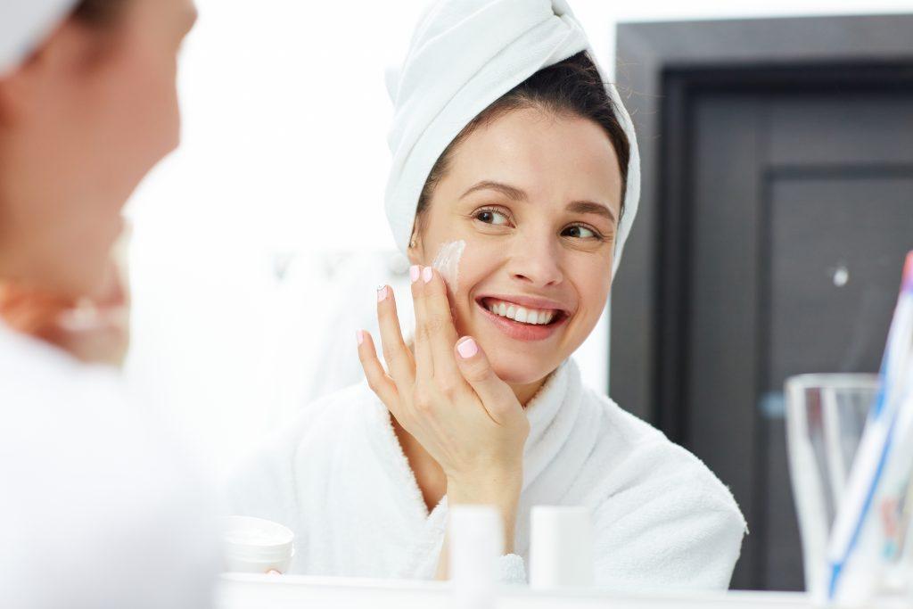 Foto mostra uma mulher usando um roupão e uma toalha enrolada nos cabelos. Ela está diante de um espelho e passa um creme na bochecha enquanto sorri.
