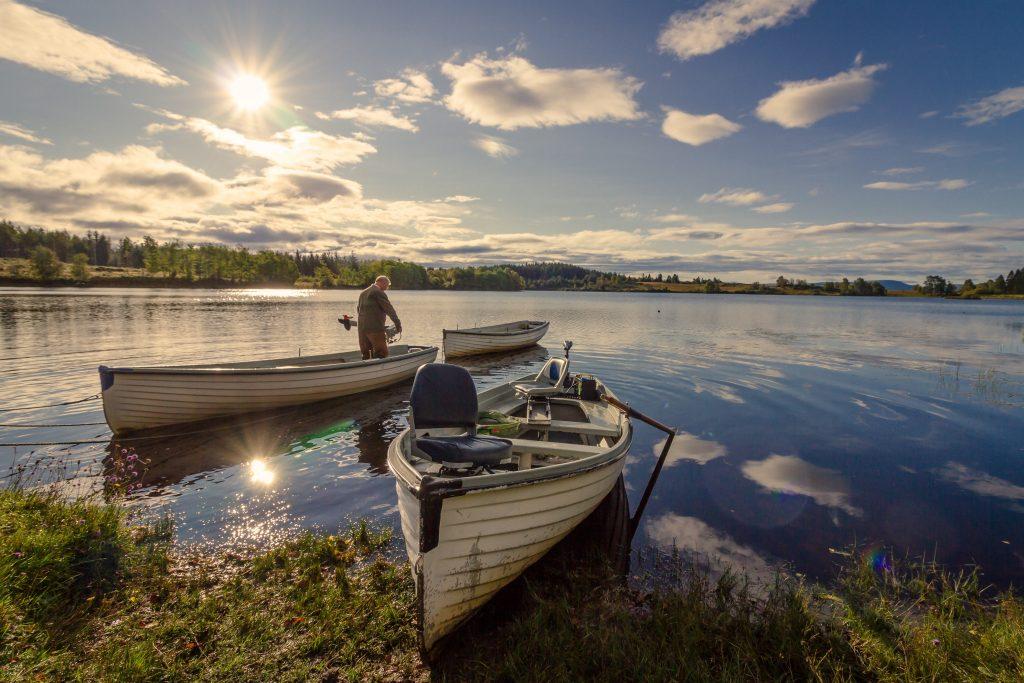 Imagem mostra um homem pescando em um barco.