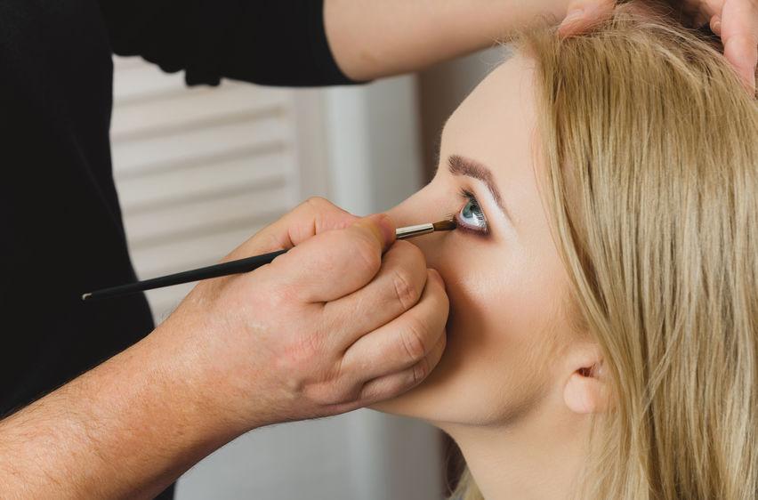 Foto de maquiador esfumando o lápis de olho na linha d'água dos olhos de uma moça loira, com a ajuda de um pincel.
