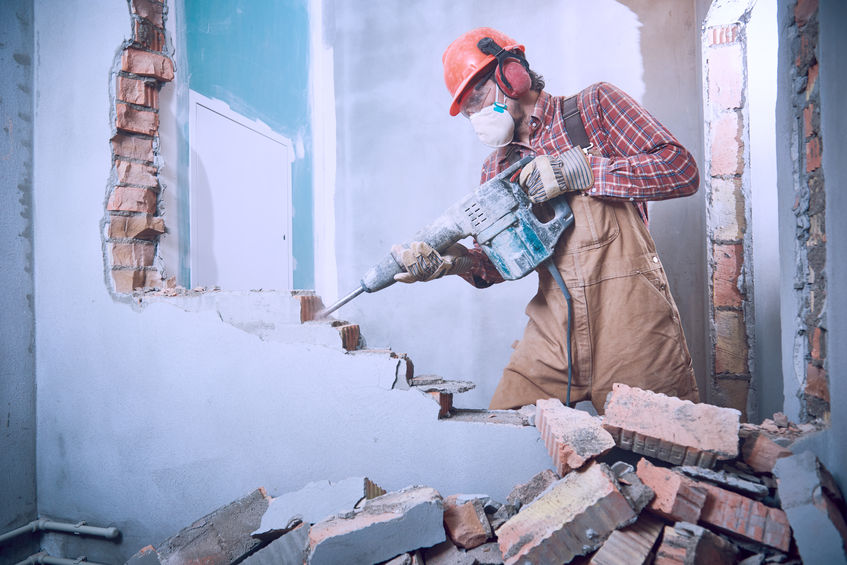 Imagem mostra um homem usando um martelete para derrubar uma parede.