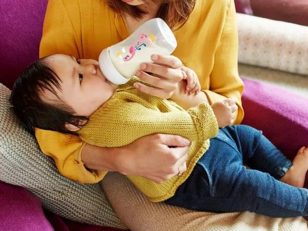 Mãe dando mamadeira para sua filha em uma mamadeira Avent.