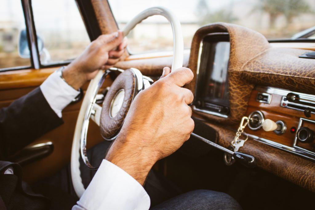 Imagem mostra uma pessoa, retratada apenas pelas suas mãos, que estão segurando o volante, pilotando um carro antigo.