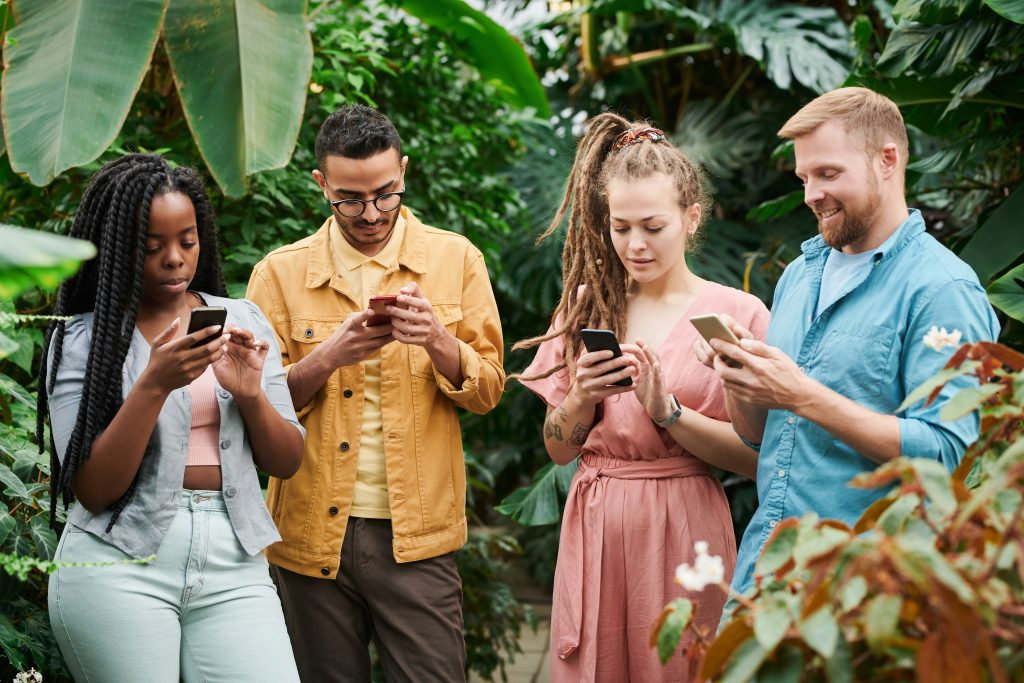 Imagem de um grupo de pessoas usando seus smartphones.