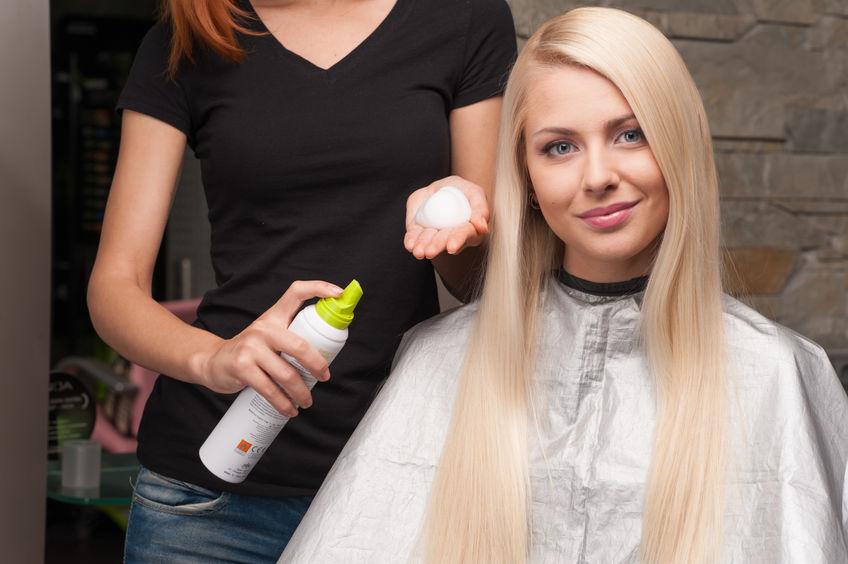 Imagem de cabeleireira segurando o mousse para cabelo antes de aplicar na cliente