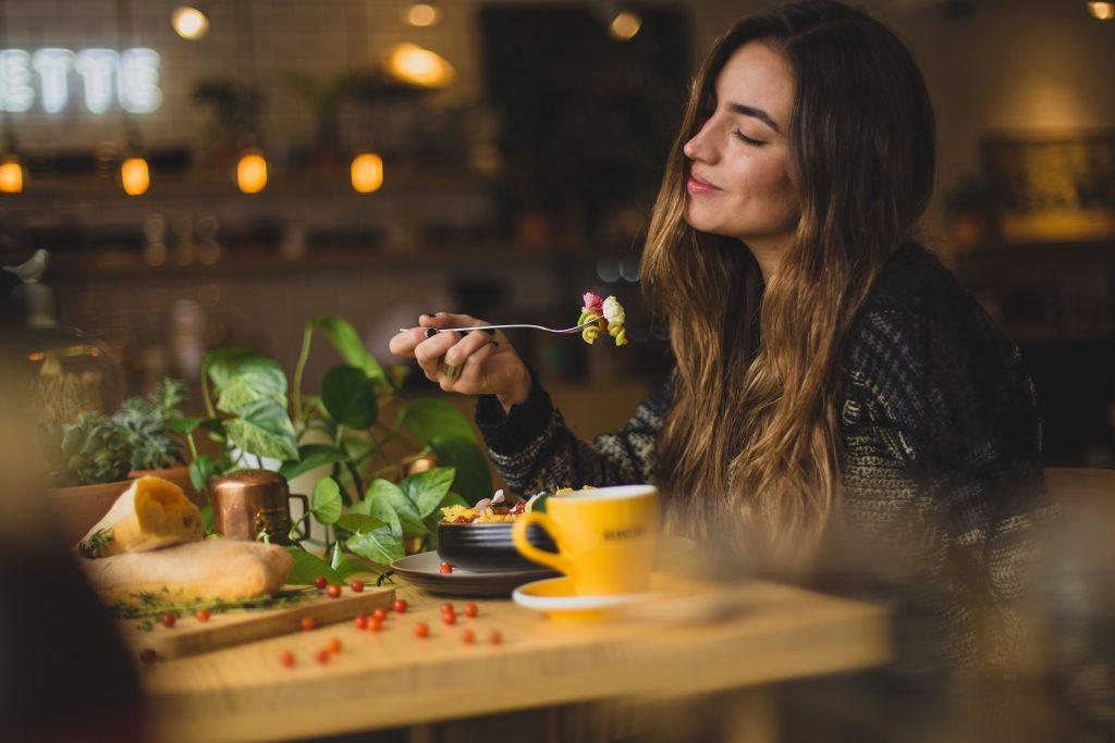 Mulher sentada a mesa comendo macarrão.