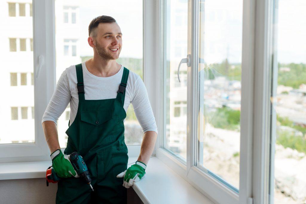 Imagem mostra um homem sorridente com uma parafusadeira em frente a uma janela.