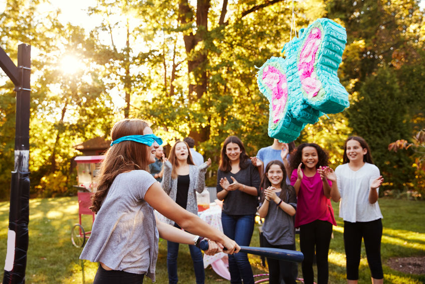 Crianças ao redor de uma pinhata de borboleta pendurada em uma árvore enquanto menina vendada tenta destruir o artigo.