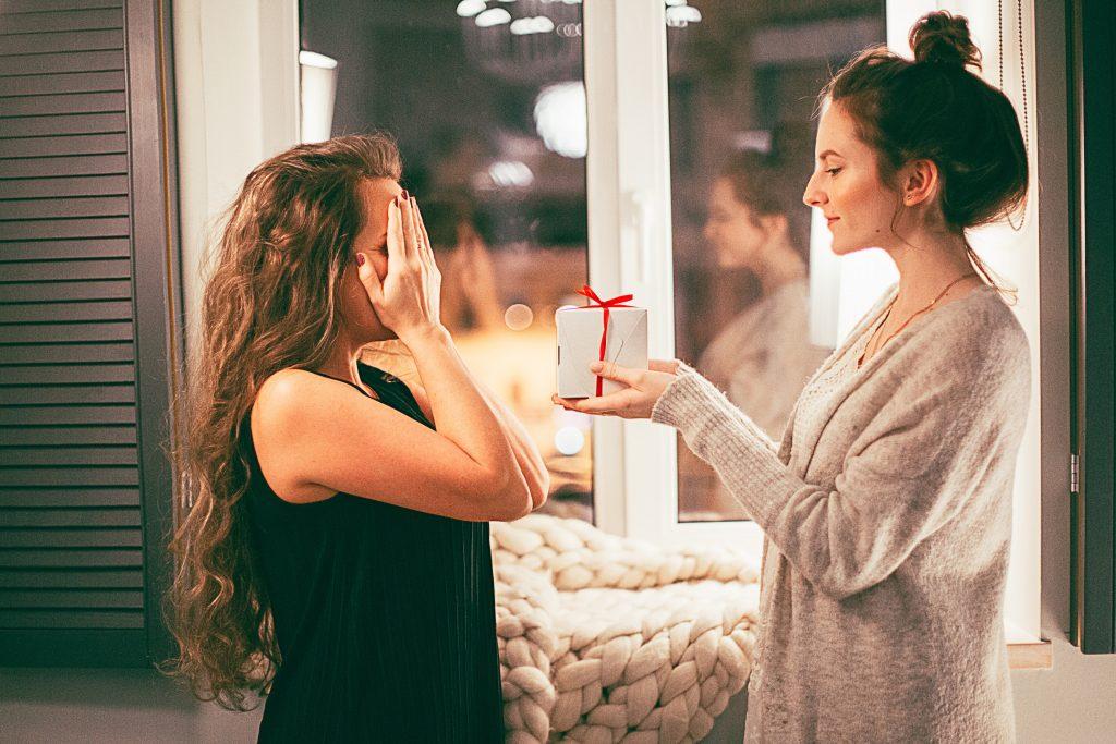 Imagem mostra uma mulher oferecendo um presente para uma mulher à sua frente, que tem o rosto coberto pelas próprias mãos.