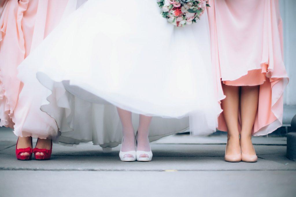 Na foto os pés de uma noiva com duas madrinhas ao lado.