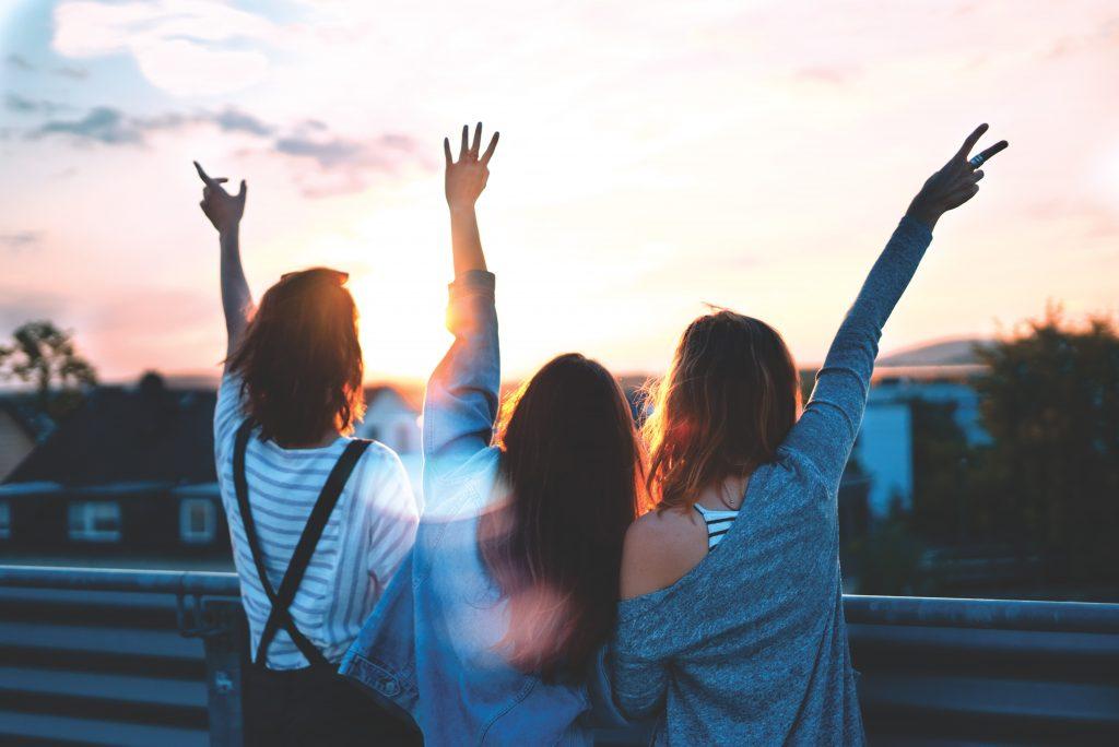 Na foto três mulheres com os braços para cima de costas.
