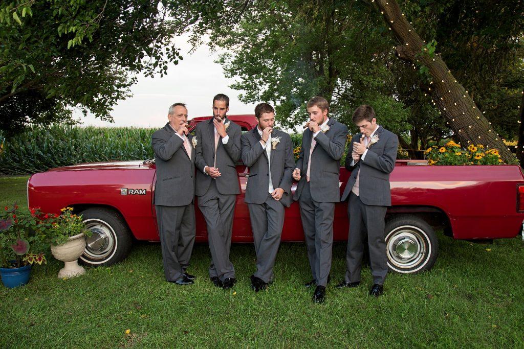 Imagem mostra cinco padrinhos, trajados de ternos, fumando charutos em frente à um carro.