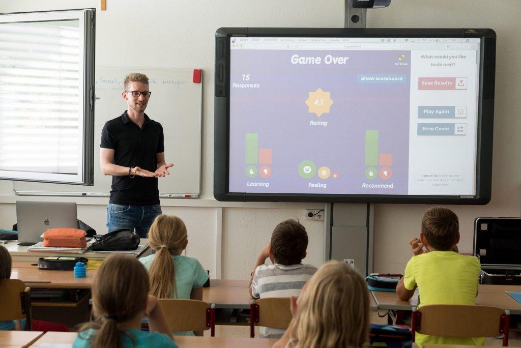 Na foto um professor em uma sala de aula com algumas crianças sentadas
