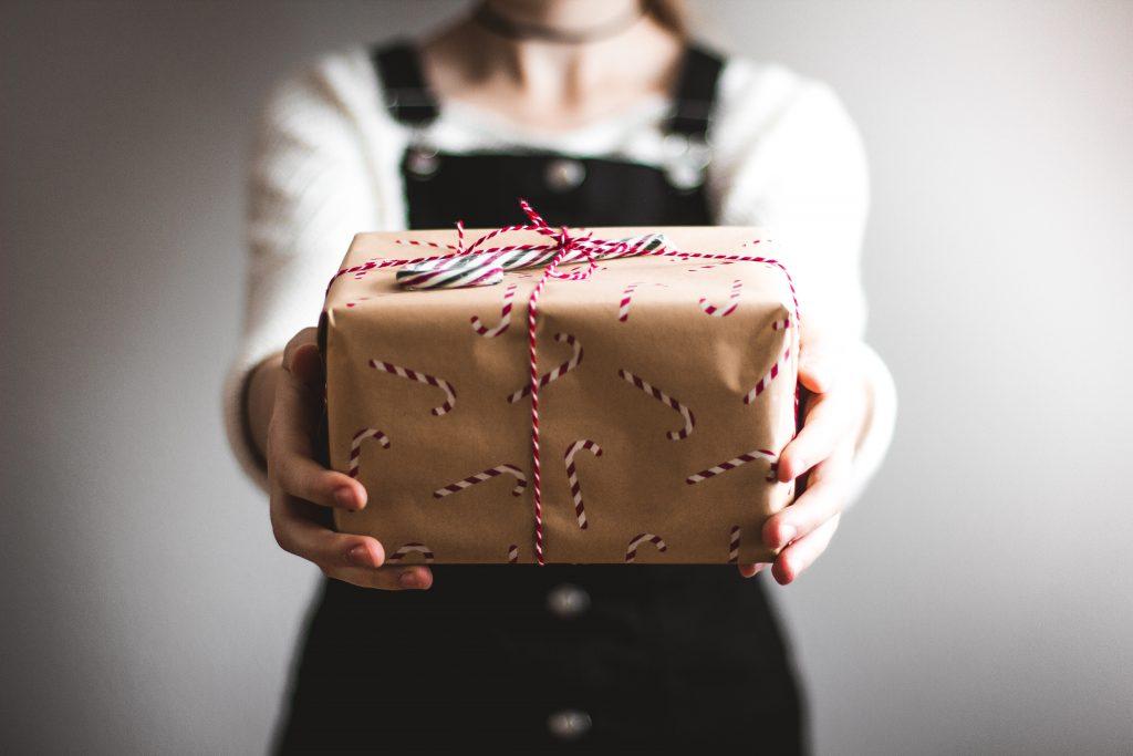 Na foto uma mulher entregando um presente.