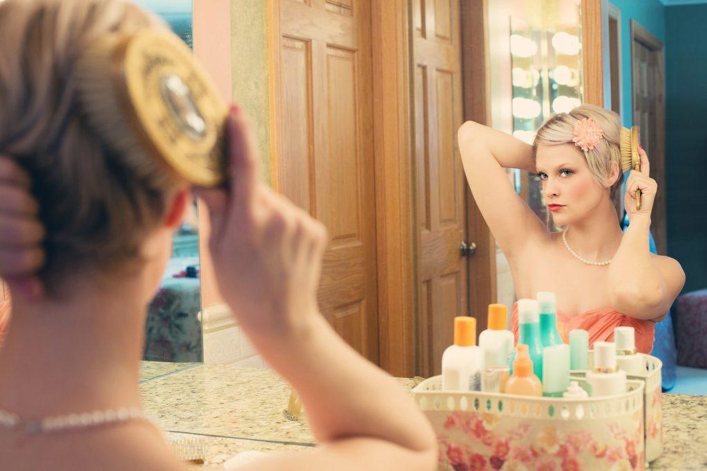 Imagem de mulher se penteando na frente do espelho após utilizar produtos Inoar