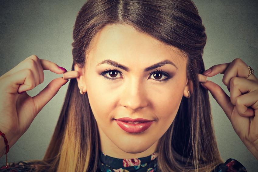 Imagem mostra uma mulher inserindo protetores auriculares nos ouvidos.