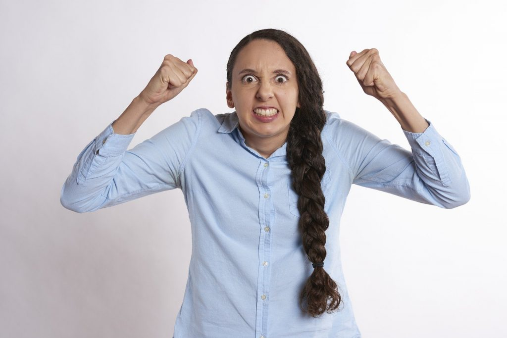 Na foto uma mulher irritada com os braços para cima.