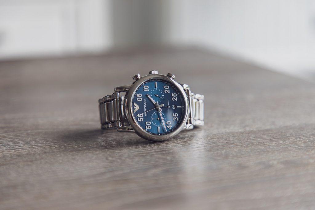 Um relógio Emporio Armani de armação prateada e fundo da tela azul está com a pulseira fechada e deitado em cima de uma mesa.
