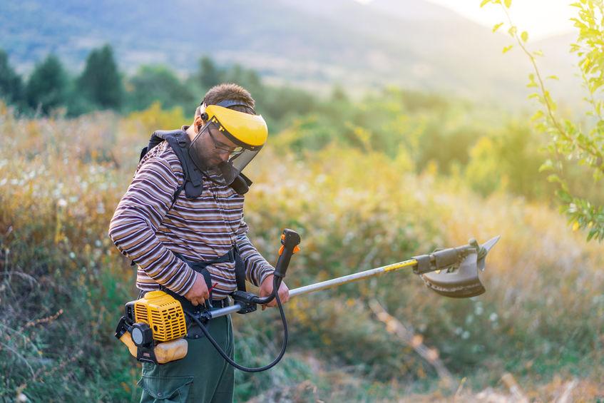 Imagem mostra um homem com uma roçadeira lateral em um grande campo.