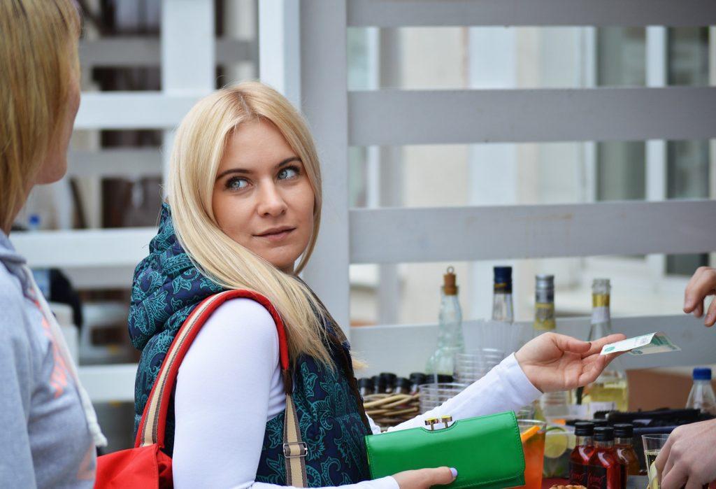 Imagem mostra uma mulher efetuando uma compra em uma loja.
