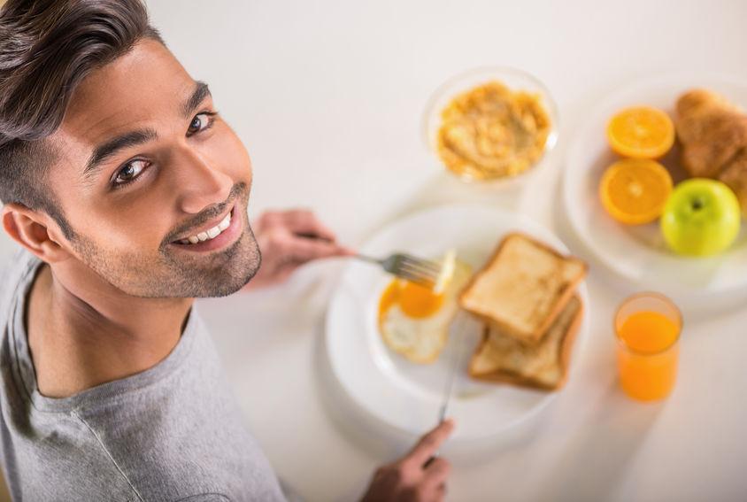 Homem sorri para foto sentado em frente a prato com torradas e ovo