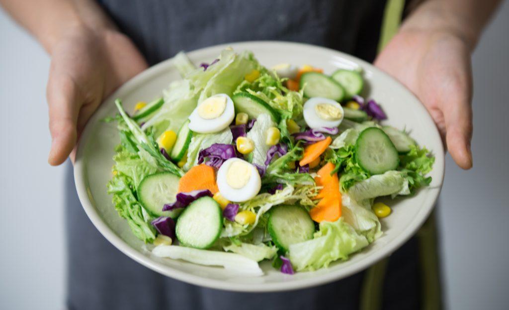 Na foto uma pessoa segurando um tigela de salada com folhas, ovos e pepino.