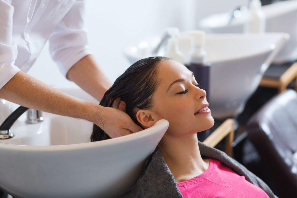 Imagem de uma pessoa lavando o cabelo no salão.
